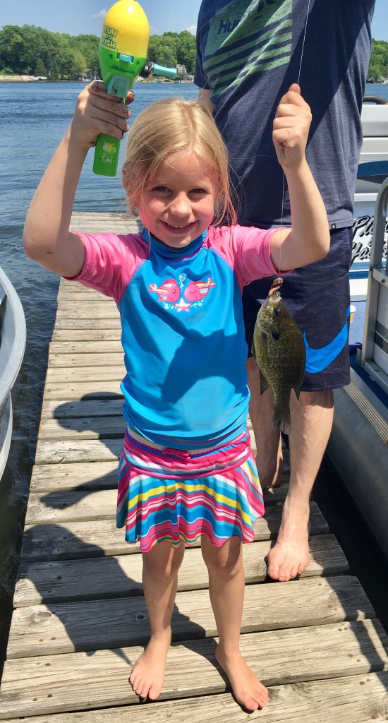 Child holding a fish for Michigan's free fishing weekend